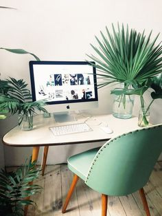 Home office space with large indoor plants, a retro desk, and a retro mint green chair