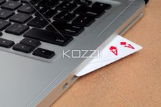 online gambling interpretation - Gambling cards inserted in a laptop symbolizing online gambling.