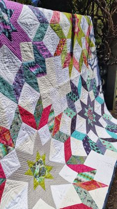 """Jess from The Elven Garden's Starburst Quilt is a fantastic array of color pulling from her collection of Tula Pink fabrics! """"I quilted it using #Aurifil 50 wt in various colours - threads from Tula Pink's Aurifil collection for the coloured fabrics, and soft white (2021) in all the background. I quilted fairly large, loose designs on this quilt, so it is beautifully drapey but still has lots of texture."""""""