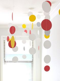 punch 2-inch circles using the yellow, gray, and coral cardstock; sew them together in random order and hang the circle strings from the ceiling (with basic transparent tape).