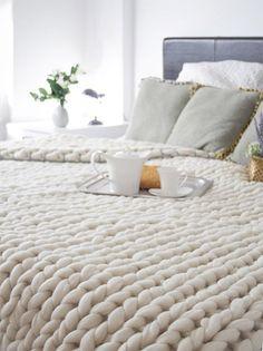 Primer plano de cubrecama de lana blanca tejido en punto grueso.