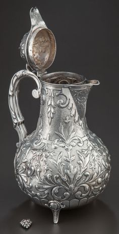 A Dutch silver wine jug from 1870, with scrolling vines and strap-work.