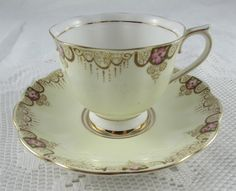Old Royal Albert Crown China tea cup and saucer. Cream coloured with a border featuring pink flowers. Gold trimming. Good vintage condition, small