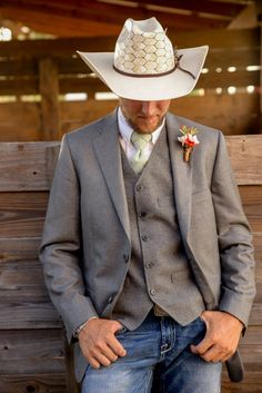 Groom attire for country western wedding. Grey suit jacket, jeans, cowboy hat and a vest with an orange boutonnière were perfect for an outdoor fall country wedding. The cowboy hat was perfect with the floating feather !