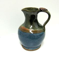 Small pouring pitcher glazed with Potters Choice vert luster on top and Potters Choice Blue Rutile on bottom.  Created by Ann Augustin Pottery, Frisco, TX.