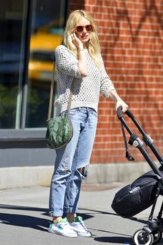 baggy ripped jeans, sneakers, a handbag and a loose fishnet...