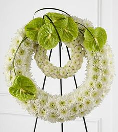 Wreath of Remembrance - White chrysanthemums and button poms are elaborately arranged to form a double wreath accented with bright green anthurium blooms and lily grass    The FTD® Wreath of Remembrance™