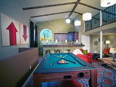 """A game room with a bar can be the perfect space for entertaining. This transitional space still has the luxury of natural light, while a vaulted ceiling minimizes any notions of it being a man """"cave."""""""