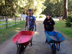 Volunteers Casey and Danyel Taking the wheel barrows out to pick up camp gear.