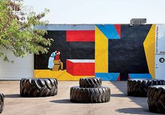 Street Food: Miami's Wynwood Kitchen & Bar | Truck tires offer a place to contemplate a Clare Rojas acrylic mural, part of the surrounding Wynwood Walls park. #design #interiordesign #interiordesignmagazine #publicart #architecture #outdoors