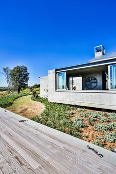 Off shutter concrete is used for the Northern facade of the modern farm house. The concrete in it self gives texture to the interior and exterior spaces. Bigger openings are possible by using concrete. #offshutterconcrete #modernfoyerdesign #landscapedesign #exclusiveliving #bigwindows #vistas #farmhouse #moderarchitecture