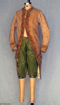 "Velvet coat and breeches, 1750-1760; Unmatched pair: 1 tan velvet with tiny red dot print, chenille embroidery in green vines and pink buds, CH 36"", L 43""; 1 pair velvet breeches, knee bands with delicate silk floral embroidery, tiny clear and red jewels interspersed and silver sequins above and below embroidery, 8.5"" fall front, brown linen lining, W 34"", L 18"""