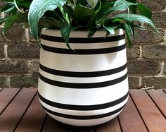 Hand-painted lightweight plant pot in blush pink and black with a metallic rose gold stripe. This is a striking design which will add a touch a glamour to your home! The material of the pot is fibreglass and painted using water-based paint. Small - 25 x 25cm Medium - 35 x 35cm Large - 45 x 45cm Our pots have their own personality and imperfections which is what makes them unique. As the pots are hand painted they are delicate and need to be handled with extra care. They are intended for…