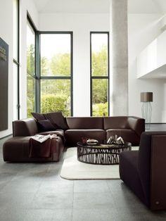 Woonkamer met hoog plafond en leren hoekbank van Rolf Benz. Een hoekbank kan een geweldige oplossing zijn als je een zitgedeelte van de kamer af wilt bakenen. Zo stel je snel en simpel een gezellige zithoek samen. Deze prachtige warme bruinleren designbank is modern, maar niet superstrak vormgegeven. Samen met de ronde salontafel een mooie tegenhanger voor het verder zo strakke interieur met hoge, smalle ramen.