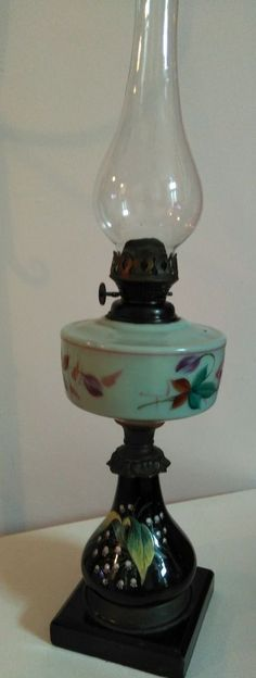 Very attractive oil lamp Black base, hand painted with Lilley of valley Pretty metalwork below burner Very pale green glass font, painted floral Includes shapely glass chimney Victorian Lighting, Vintage Lighting, Antique Lamps, Vintage Lamps, Vintage Decor, Hurricane Oil Lamps, Old Lanterns, Kerosene Lamp, Oil Candles