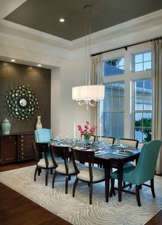 Formal dining  room. I love the turquoise arm chairs & chandelier.