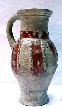 Rouen ware jug; painted bands of red slip between vertical and diagonal applied rouletted strips around body, with applied pellets over red slip; horizontal band of red slip and applied pellets around base of neck; rim and most of neck missing; base of rod handle; thin, abraded clear lead glaze overall; base reconstructed; cordon visible just above base. Medieval 13thC  Made in: Rouen,  Rouen Ware Dimensions     Height: 274 millimetres     Width: 168 millimetres     Depth: 139 millimetres