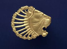 Plaque in form of a lion's head, Gold.   Centimetres: 4.9 (height), 0.2 (depth), 5.7 (width).   450-350 BC, Iron Age; Achaemenid; circa 400 BC; Hamadan phase; 5th century BC.   Area of Origin: Hamadan; Iran; Persia