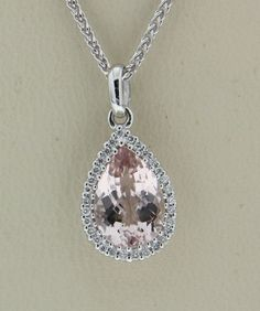 Morganite and Diamond 18 karat White gold pendant, set with one pear-shaped checkerboard cut Morganite weighing 1.73 carats, surrounded by 30 round brilliant cut Diamonds weighing a total of .10 carat.