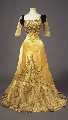 Woman's evening dress, by Atelier Worth, Paris, 1900-05, at the Pitti Palace Costume Gallery. Citron-colored silk satin dress, with floral embroidered applications in laminated wire and rhinestones on mechanical lace, studded with gold sequins. Sheer neckline and half sleeves with shoulders trimmed with black velvet and a big bow on the left. Corolla-shaped skirt with sash at the waist. Via Europeana Fashion Tumblr.