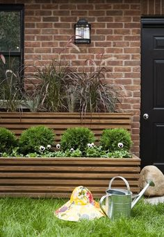 Streamlined Front Yard    An array of horizontal lines brings definition and depth to a garden.      Two-tiered cedar planters house billowy grasses, globe cedars and pansies added for annual colour. Painting the door and window trim black makes them pop against the red brick façade.    Photographer: Stacey Brandford  Source: House & Home September 2007 issue #curbappeal #smallgarden #frontyard