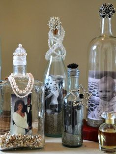 Display Photos in Upcycled Bottles | how-tos | DIY Tools hot-glue gun long-handle paintbrush or pencil with eraser Materials clear wine or liquor bottles small seashells sand bendable copper wire bottle toppers (corks or fun items like an old door knob) candle
