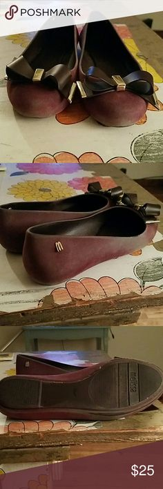 Melissa Space Love Flock used flats Beautiful Melissa brand flats in a pretty plum color with cool bows on the toe end and gold detailing. Tread and interior are in good condition but outside has some discoloration of the purple to grey. Not terribly noticeable but still there. One little area is peeling, contact me if you want more pics. Pretty good condition. Outer is flock not the jelly kind, made in Brazil. On bottom says size Euro 37. Melissa Shoes Flats & Loafers