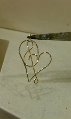 For the music lover. 14 k white and yellow gold wire pendant.