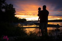 Silhouette of father and son watching the sunset on Mullet Lake, Michigan