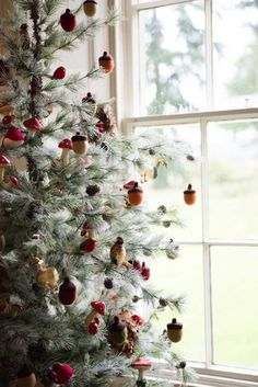 CHRISTMAS DECORATIONS THEME: ENCHANTED FOREST. This Frosty Tree (coming soon) is adorned in V V Rouleaux's cream acorns, bronze glass pheasants, green acorns, red acorns, glass toadstools, glitzy Christmas geese, robins, red mushroom clusters, and brown feather wreaths.