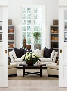 simple, relaxed living room. Pocket doors, earthy accents, and white