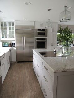 White kitchen with light wood floors and solid stainless appliances.