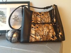 """""""Victoria's Safari""""   This custom order medium sized purse features soft black vinyl trimmed with some big cat cotton fabric.  A large exterior pocket and a hand made tassel with wooden beads makes this bag meow worthy!  Check out Bobbin My Thread on Facebook for more designs by Nena."""
