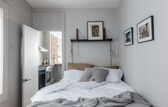 Gray cozy bedroom with jute pillows, grey Madrugada cushion by Abigail Ahern, Breezy grey throw and dark wood and leather shelf (CB2).