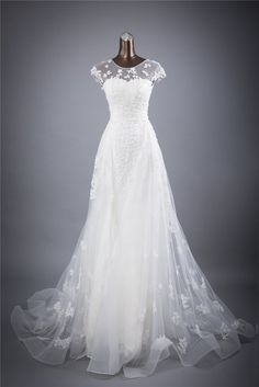 Beautiful vintage style, A-Line dress with floor length organza dress covered in floral lace and tulle. Natural neckline, lace applique cap-sleeves, semi-backless, with lace tie-up back and court trai