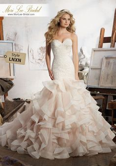 Style LNXN Maisie Wedding Dress  Stunning Mermaid Wedding Dress Featuring Allover Embroidery on Net with Horsehair Edged, Flounced Organza Skirt. Covered Buttons Along Back. Available in Three Lengths: 55″, 58″, 61″. Colors Available: White, Ivory, Ivory/Caramel. Shown in Ivory/Caramel.
