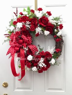 Large Red Roses, and tiny Red and White Rosebuds abound in this romantic Spring and Summer beauty! The brilliant reds contrasted with bright whites make this gorgeous wreath a head turner! Bringing it all together is large, perky bow made of red polka dotted ribbon and red satin ribbon.  This is your doors perfect spring and summer decor! Its perfect for Valentines Day!  The base is an 18 inch grapevine wreath. It measures about 25 inches up and down, and about 22 inches across. The depth is…