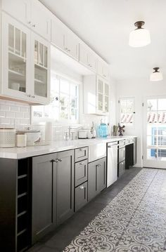 White and black kitchen features glass upper cabinets and black lower cabinets paired with white quartz countertops and a white beveled subway tile backsplash.