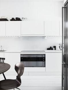 cocina, estilo nórdico, muebles blancos sin tiradores, paredes y suelo de parquet en color blanco, mesa y sillas de madera en tonalidad oscura, elementos decorativos en color negro