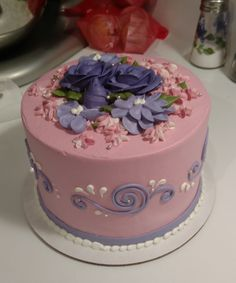 A cute pink cake with flowers, scrollwork, and silver dragees.