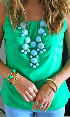 green blouse.  blue necklace.  blue jeans.  turquoise necklace.  turquoise jeans love love