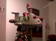 Elf on the shelf in airplane with fishing line in doorway