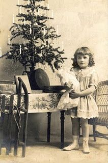 Little girl with doll, with Christmas tree.