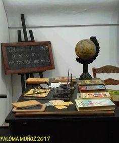 La mesa del profesor y estantes se ven algunos manuales, métodos de lectoescritura y libros de urbanidad.  Pizarra con la lección de gramática escrita a tiza The teacher's table and shelves are some manuals, methods of literacy and books of civility.