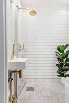 Marble looking tile floor. Brass shower head. Gorgeous small sink with brass faucets. Loving the plant in the wetroom.