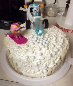 "DIY paw patrol Everest cake! Need: two 9"" cakes, frosted with white buttercream. 9 white chocolate kit kats and ""snowballs"" I used white coated chocolate candy balls found at local grocery  store in baking section ."
