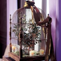 Cage à oiseau en fer décorée de mousse, bougies parfumées et bouquet de branches pour un décor de fête