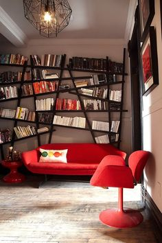 Snazzy bookshelf draws your attention instantly despite bright red decor! [From: Lisa Petrole Photography]