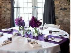 Simple and eclectic centerpiece of purple hydrangea and stock in medium sized bud vases with a purple satin runner