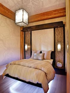 "A simple design and Asian-influenced accents give this bedroom a meditative ambiance. Says designer Jacqueline Glass: ""In this eco-friendly home, the all-in-one bed, end tables, and lighting panel are a clever way to have it all in a room short on space. LED lighting under the bed frame gives the illusion that it's floating. The natural wood walls and flooring provide a nature-inspired backdrop for this soothing bedroom escape."""